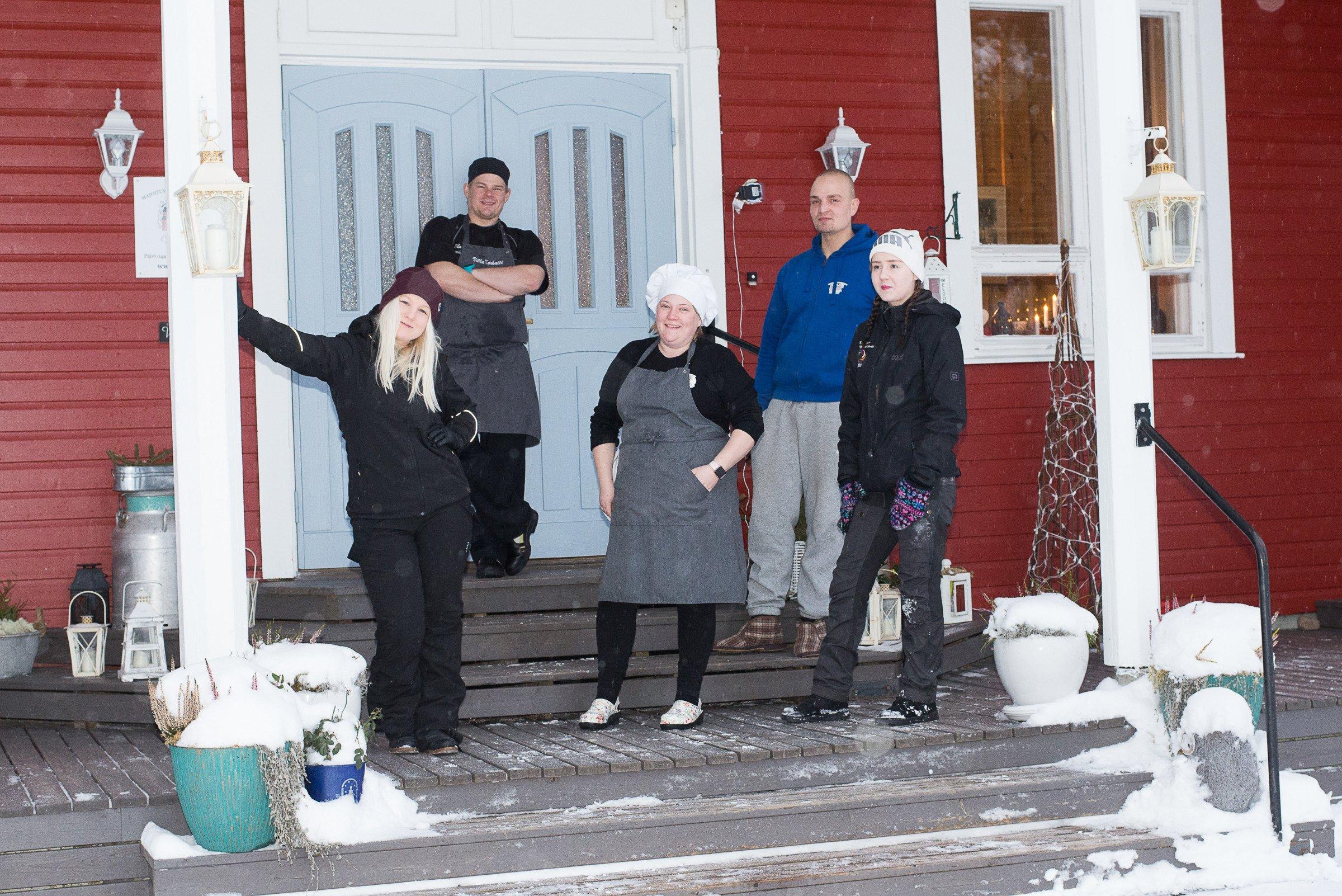 Viisi henkilö rakennuksen portailla