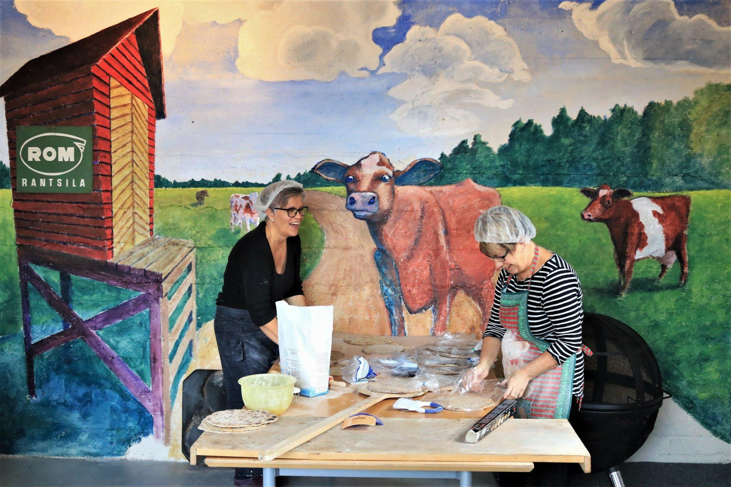 Naisia leipomassa lehmämaalauksen edessä